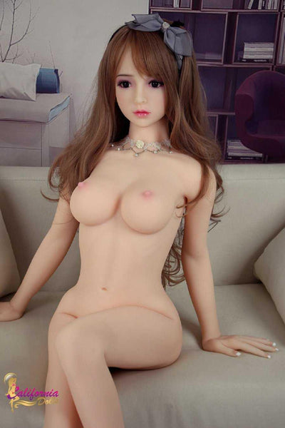 Pretty Japanese sex doll sits on couch naked.