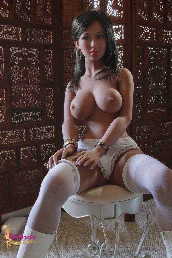 Tall sex doll sits on chair topless.