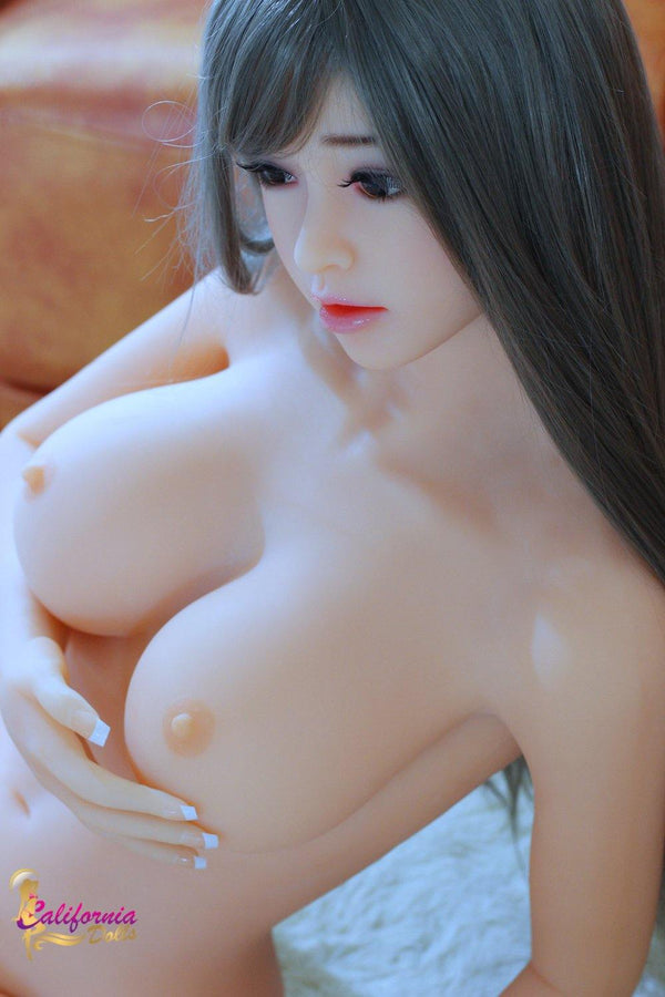 Robotic sex doll holds nude tits with hand.