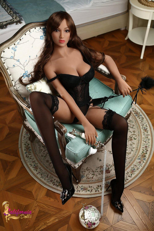 Sex doll holds telephone between slender legs.