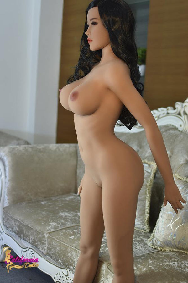 Nude Japanese sex doll standing by couch.