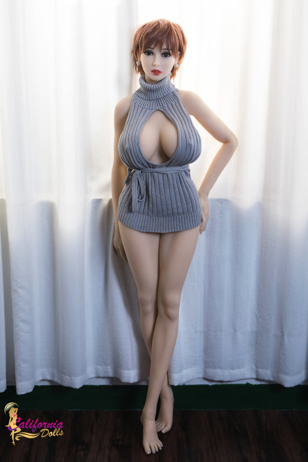 Tall big bust sex doll stands, youthful legs uncovered.