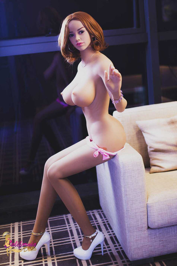Brunette sex doll sits on couch arm rest.