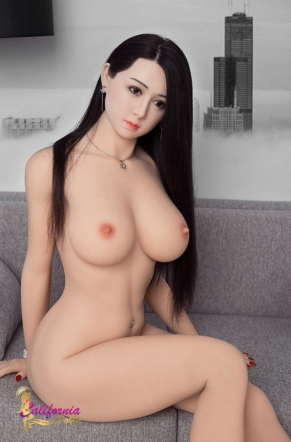 Full naked Japanese doll sits on sofa