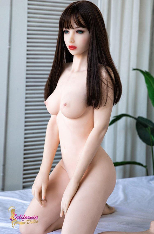 Small breast sex doll lying on bed naked.