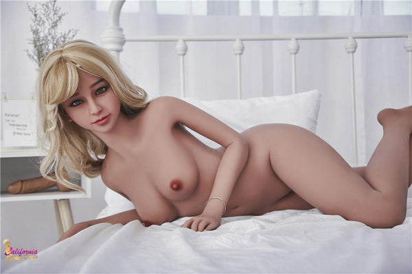 Teasingly Kerry on bed with legs crossed and showing off her  small breast and pretty face.