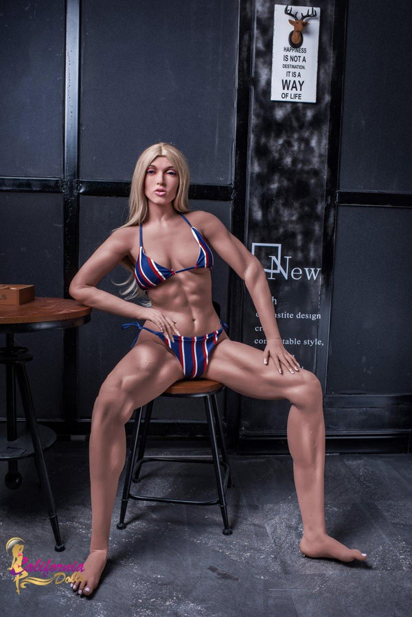 Body builder blonde sex doll sits with legs open.