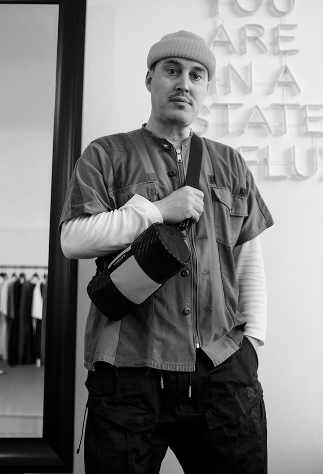 Image of Brandon McCarthy standing in the State of Flux store, looking at the camera as he holds a Mini Hustle Duffel State of Flux Edition on his shoulder.
