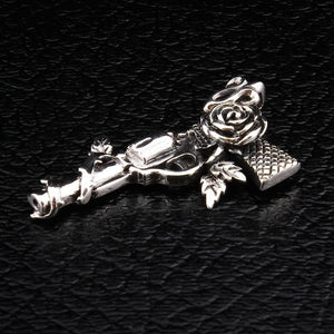silver gun and rose pendant