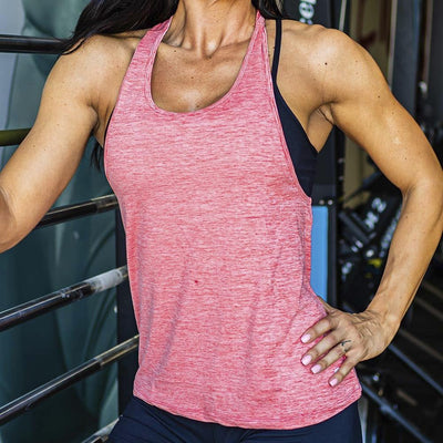 Front view of a lady wearing a pink coral colored tank top with her hand on her left hip