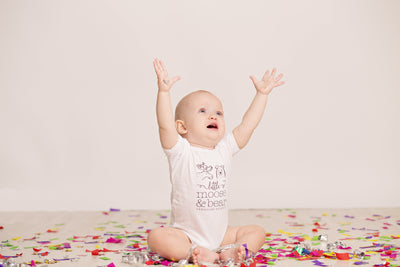 Happy baby, arms up with excitement. Baby is wearing white gender neutral onesie