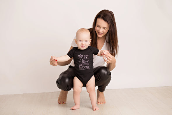 Smiling baby and mom, baby is wearing black onesie with white LMB original design.
