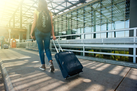 Woman walking in airport with suitcase