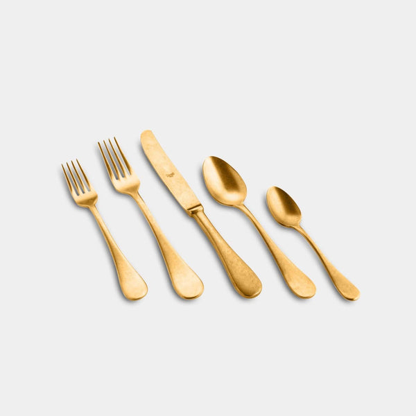 Made in Italy the matte gold five piece flatware set makes for a timeless plate setting: fork, knife, spoon, salad fork, and dessert spoon.
