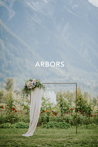 Tofino Wedding Flowers - Wild Bloom Floral Design - piped ceremony arbor with flowing linen piece with floral adornments on left corner mountainous background