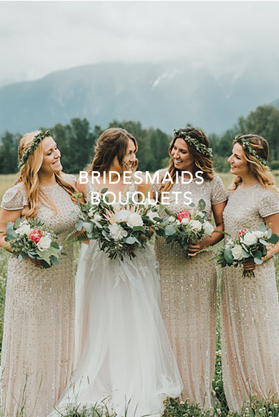 Tofino Wedding Flowers - Wild Bloom Floral Design - bride and three bridesmaids each holding different bouquets in meadow with summer mountain in background
