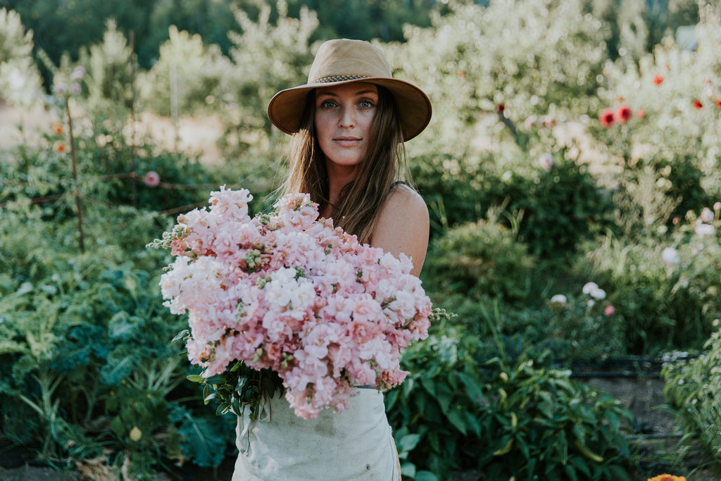 Master Florist  - Darcey Welch - of Wild Bloom Floral Design - in the garden with a sun hat and holding an armful of light pink blooms - Tofino Wedding Flowers