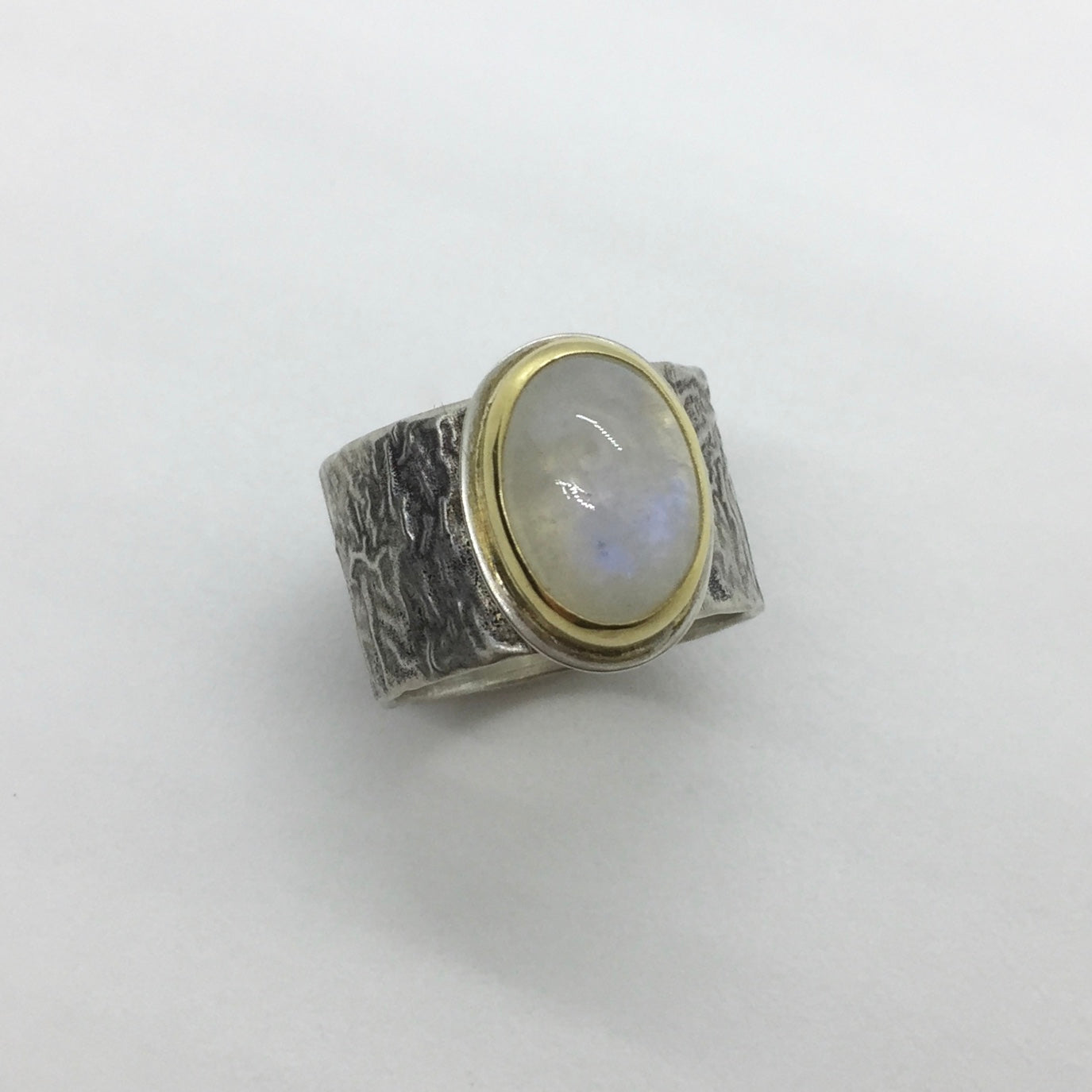 Rainbow Moonstone set in 18k gold bezel and reticulated silver band