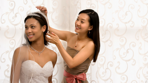 black bride sitting while asian lady puts a tiara on her head