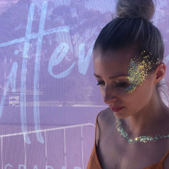 Stunning blonde woman with her hair pulled back and Glitterazzi's signature look; temple glitter. Example of glitter pulled back into the hair for affect.