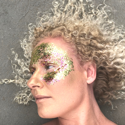 Emily Shurey co-founder glitterazzi wearing mask of gold and pink glitter