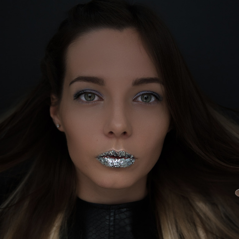 Lady wearing sliver glitter on her lips in a dark room