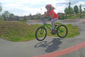 Gir lriding on Nanaimo pump track on green Cleary bike