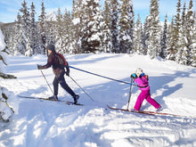 Adult towing child on cross country skis with the blue Winter / All Season TowWhee