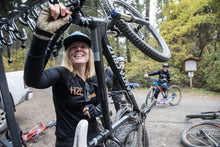 Lolo Rack - Woman loading her mountain bike on a the best 6 bike vertical rack
