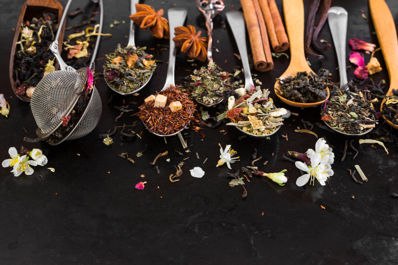 A variety of loose leaf tea scatter on wooden spoons including jasmine flower, rose petals, tight oolong tea balls, lemongrass, rooibos, Chai spice mix such as cinnamon sticks