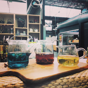 3 glass teapots of different tea liquor. A blue pea tea, a oolong tea, and a rooibos tea