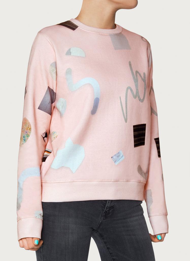 Woman with wearable art sweatshirt on. Pink-coloured hoodie, minimalistic design, made from sustainable material. Front picture.