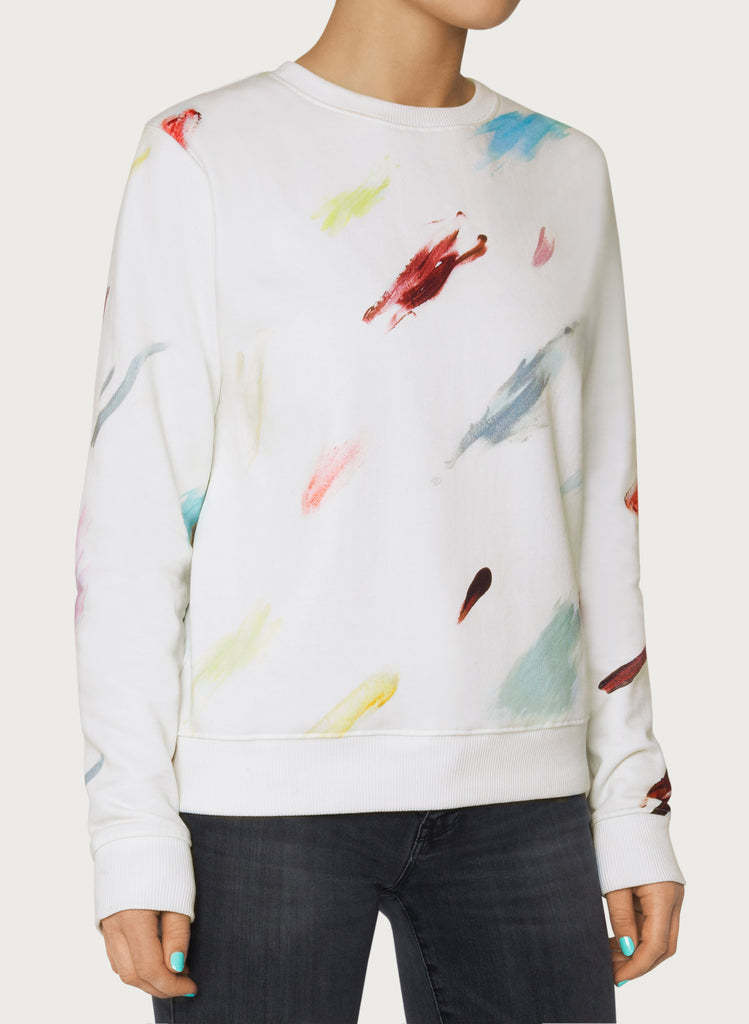 Female model wearing white sweatshirt with colourful artistic design. Wearable art hoodie made from organic cotton material. Front picture.