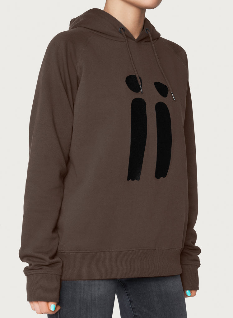 Female model presenting brown, unisex sweatshirt with ARTiiG logo on. Wearable art hoodie for him and her. Front picture.