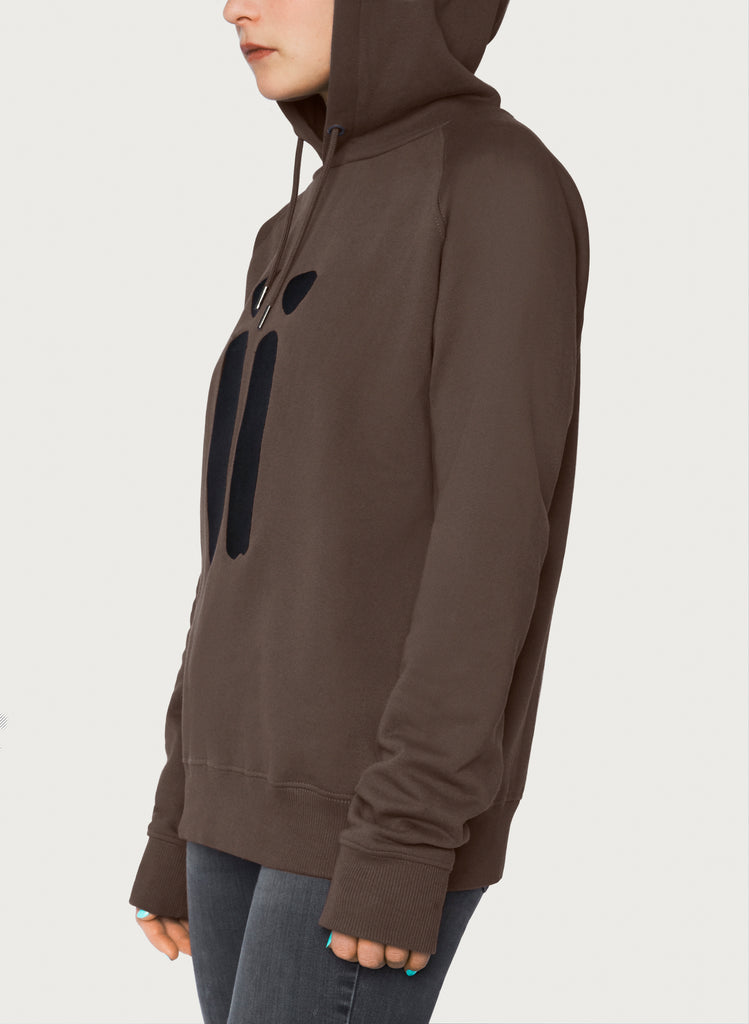 Female model presenting brown, unisex sweatshirt with ARTiiG logo on. Wearable art hoodie for him and her. Side view.
