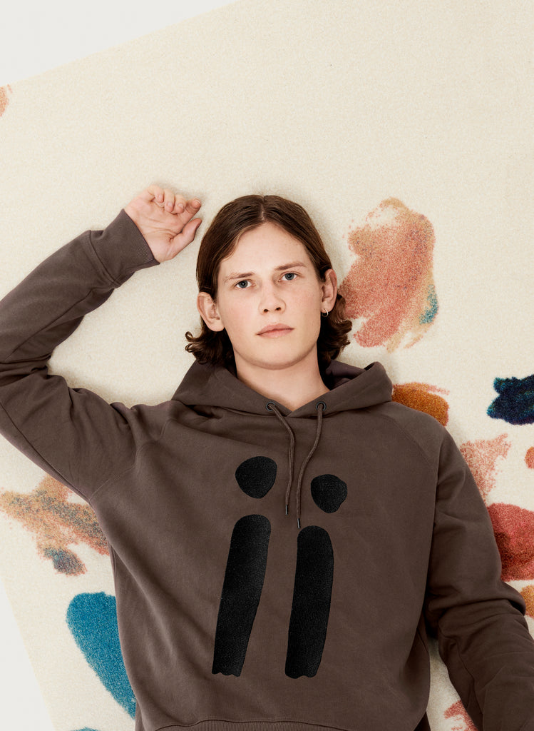 Male model presenting brown, unisex sweatshirt with ARTiiG logo on. Wearable art hoodie for him and her. Artistic version.