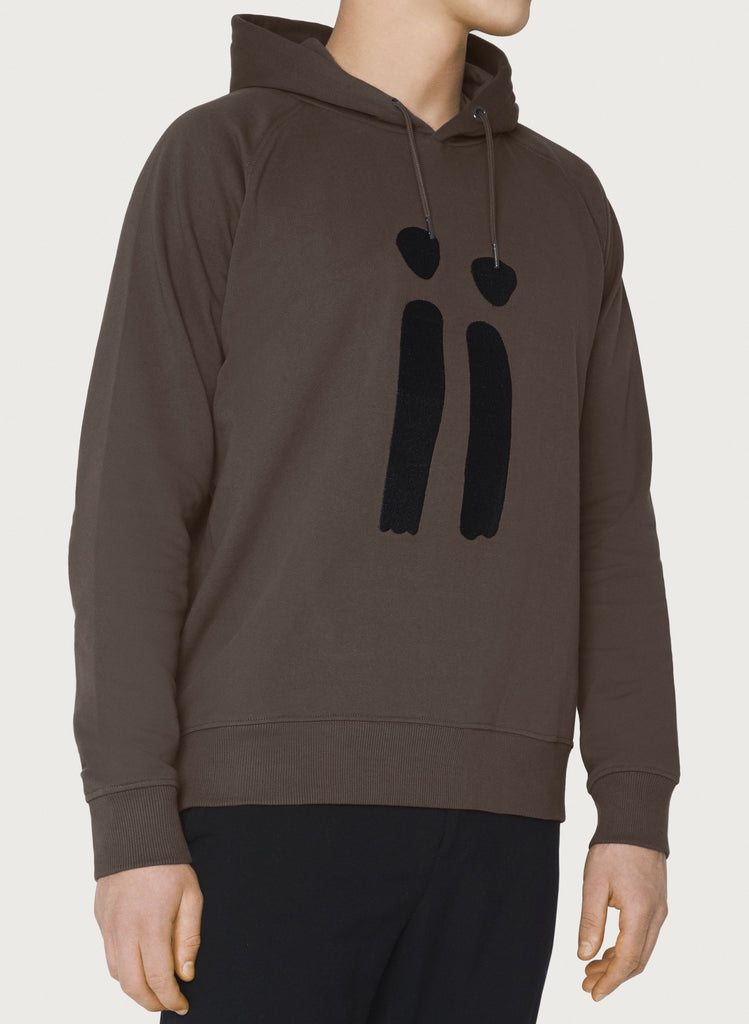 Male model presenting brown, unisex sweatshirt with ARTiiG logo on. Wearable art hoodie for him and her. Front picture.