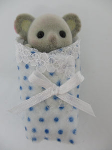Sylvanian Baby cuddle rug white background with blue spots.Edged with white lace and has a white ribbon at the front.