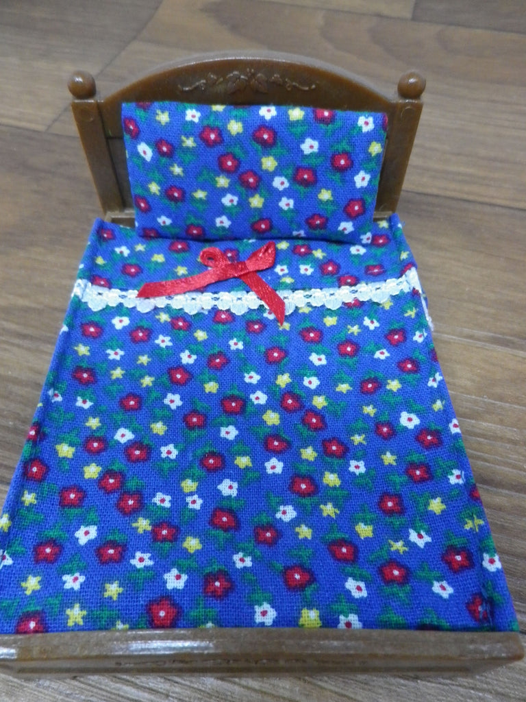 Sylvanian Double bed royal blue background with red,white and yellow flowers.Has white lace trim and a red bow on the front.A matching pillow to complete the set.