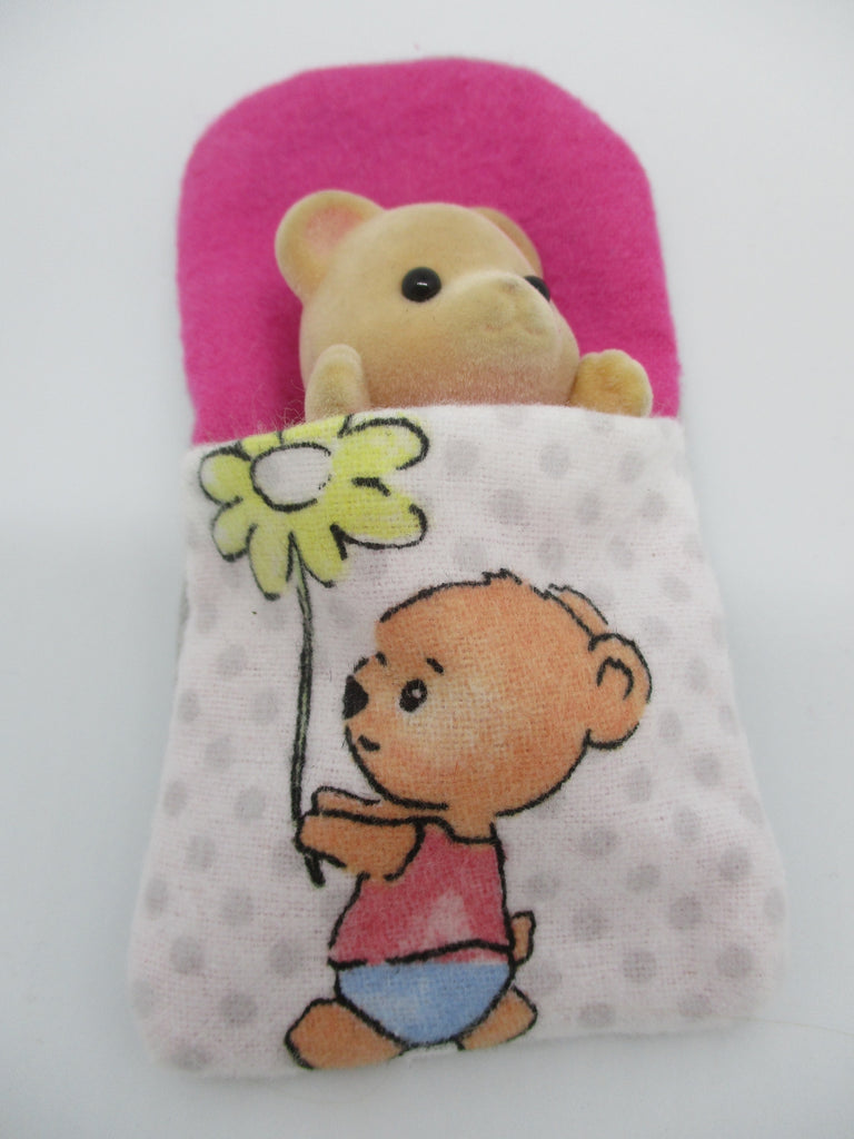 Sylvanian Families Sleeping bag with teddy bear holding a daisy flower on the front,lined on the inside with pink fabric.