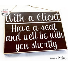 Load image into Gallery viewer, 10x8 With a Client Have a Seat and We'll Be With You Shortly Custom Wood Sign Salon Spa Office Please Have a Seat In Session Meeting Plaque