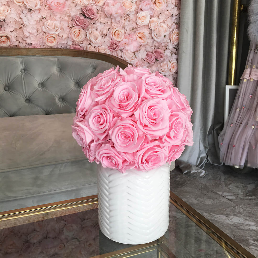 Bridal bouquet of pink preserved roses in a white vase