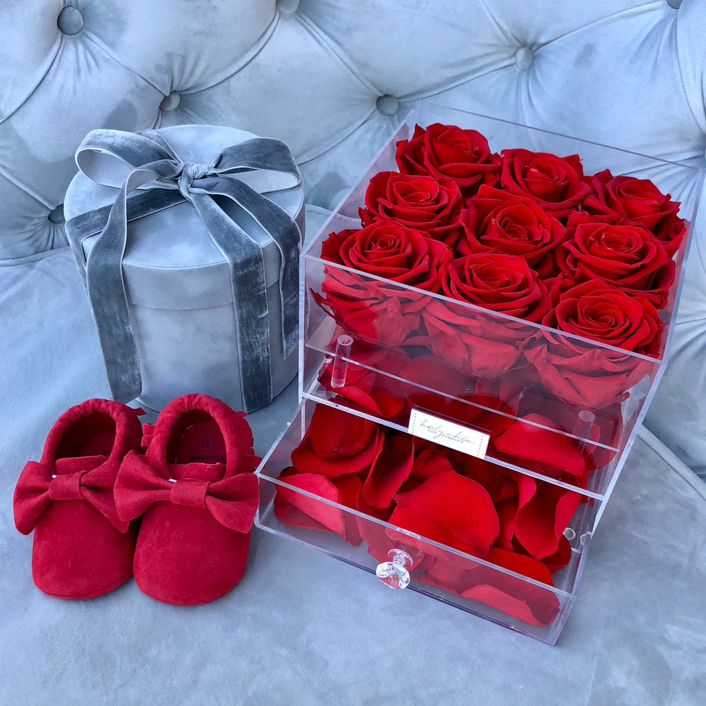 Preserved roses in a in transparent acrylic square box with a drawer full of rose petals
