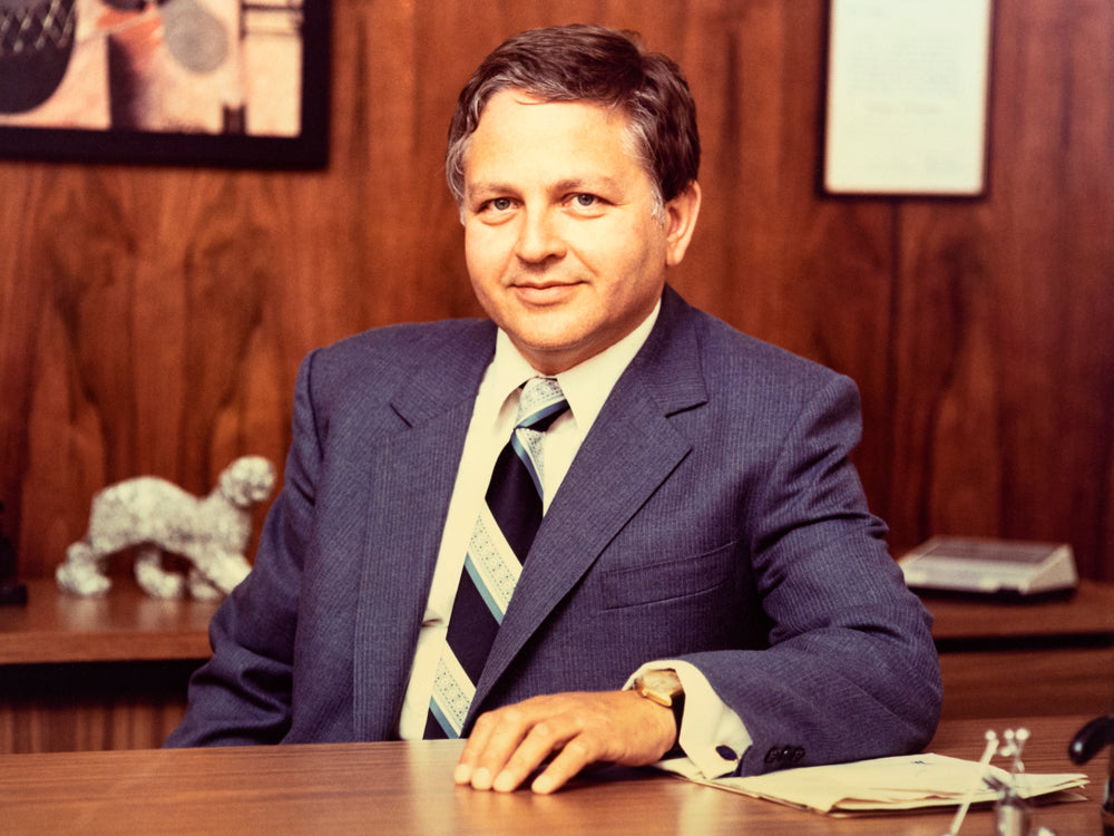 color photo of Leon Wein sitting behind a desk in a suit and tie