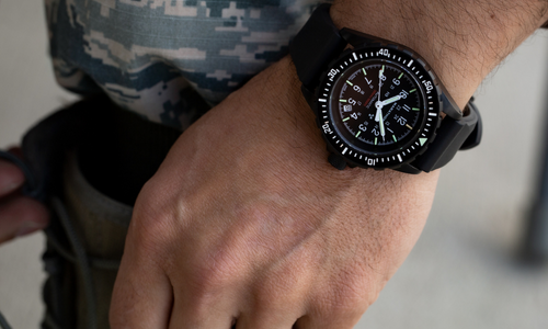 Closeup of a watch on the wrist of someone wearing military fatigues