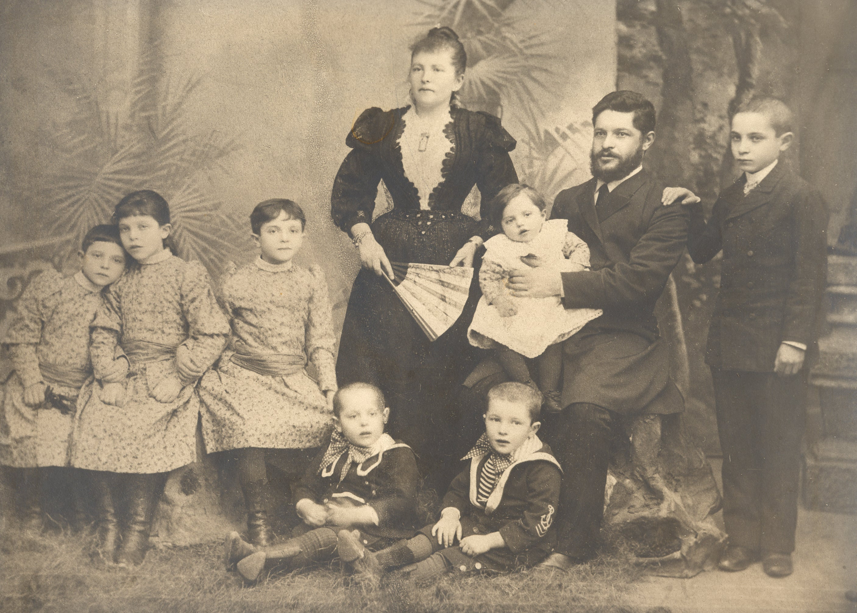 black and white photo of the Wein family: the father sitting holding a baby and the oldest son's hand on his shoulder, the mother standing with a fan, two toddlers at her feet, and three young girls sitting to the left of her