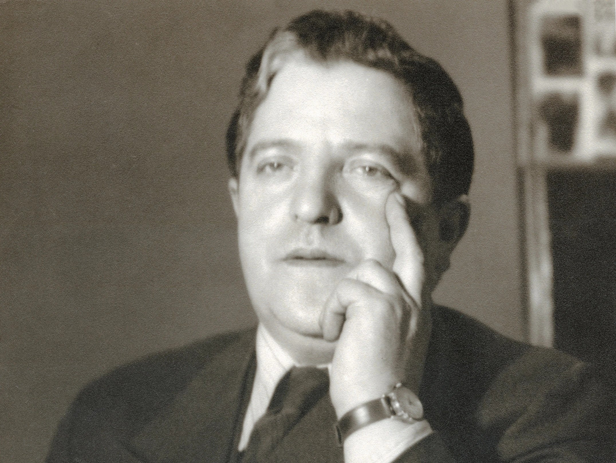 black and white photo of Morris Wein with his left hand on his cheek