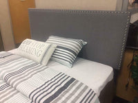 Grey upholtered bed with nailhead headboard C350071
