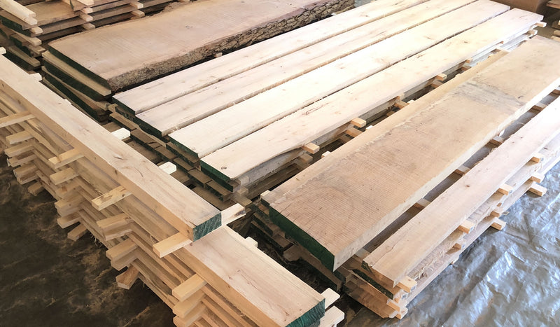 Freshly milled lumber stacked for drying.