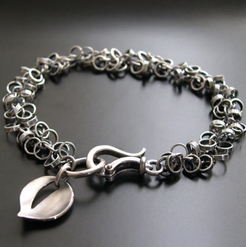 A silver bracelet with a leaf charm